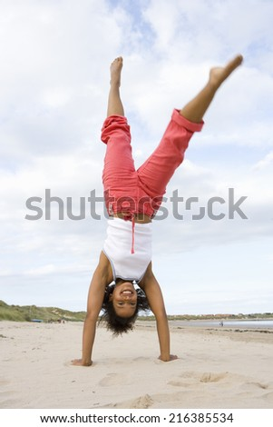 Young woman doing cartwheel on beach - stock photo