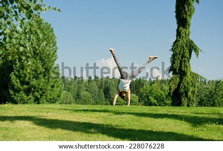 Young woman doing cartwheel outside