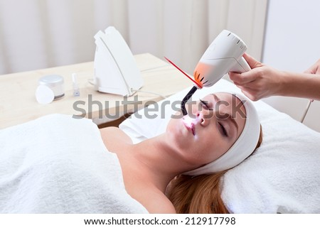young woman doing cosmetic procedures in spa clinic