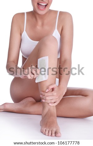 young woman doing depilation for her legs with waxing - stock photo