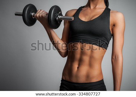 young woman doing exercise with dumbbell