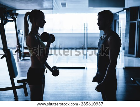 Young woman doing exercise with dumbbells with her trainer near by