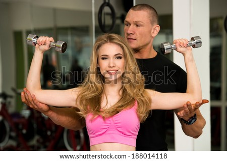 Young woman doing exercise with the help of a personal trainer at the gym