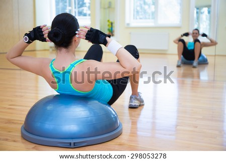 young woman doing exercises on bosu ball in gym - stock photo