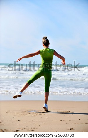 young woman doing exercises on the beach - stock photo