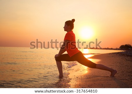 Young woman doing exercises on the beach at sunset.