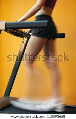 young woman doing exercises on treadmill. close up legs - stock photo