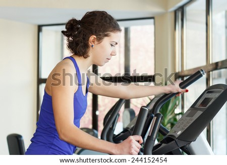 Young woman doing exercises with elliptical trainer in gym - stock photo