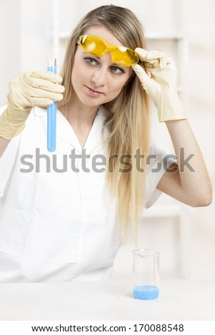 young woman doing experiment in laboratory - stock photo