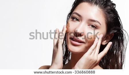 Young woman doing facial peels coffee scrub - stock photo