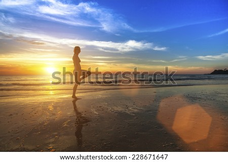 Young woman doing fitness on the ocean beach during the amazing sunset.