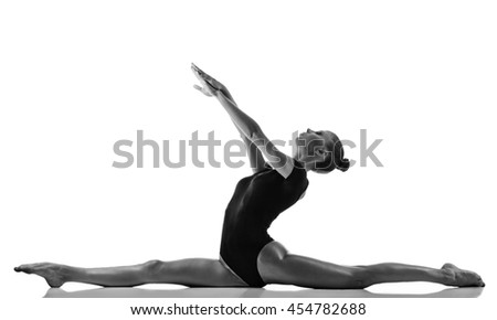 Young woman doing gymnastics exercise on white background. Black white image