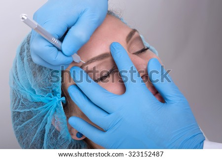 Young woman doing her eyebrows done