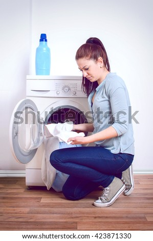 Young woman doing laundry  - stock photo