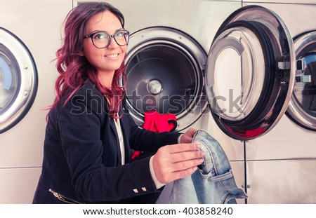Young woman doing laundry in laundromat shop - Smiling girl laundering and looking up - Concept of daily housework and alternative ways to save time and energy - stock photo