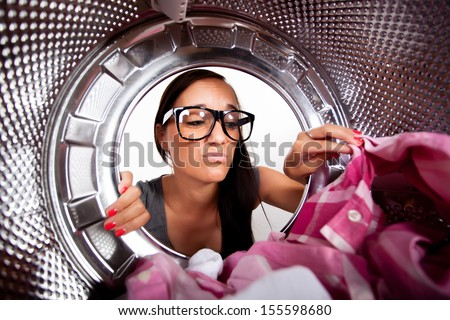 Young woman doing laundry View from the inside of washing machine.  - stock photo