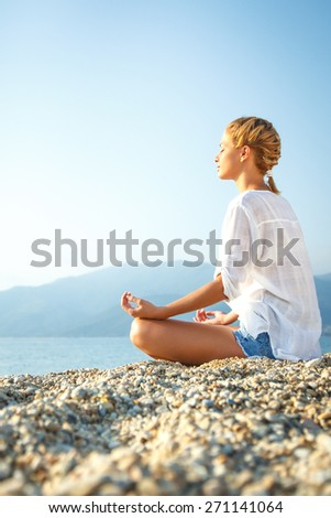 Young Woman doing meditation in lotus position on the beach. - stock photo