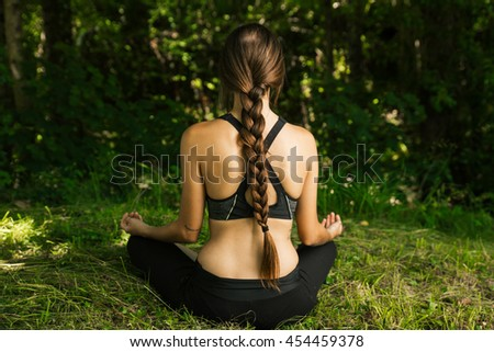 Young woman doing meditation in nature - stock photo