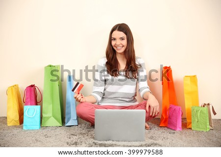 Young woman doing online shopping with laptop and credit card indoors