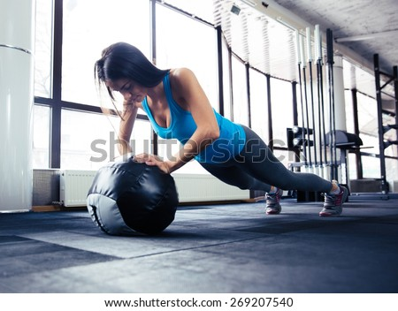 Young woman doing push up on fit ball at gym - stock photo