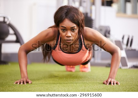 Young woman doing push ups at a gym - stock photo