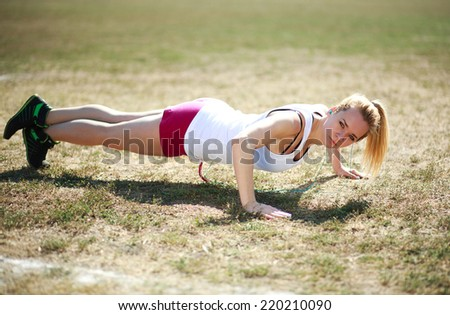 Young woman doing push ups exercise, workout on grass field - stock photo