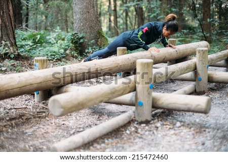 Young woman doing push ups in the woods - stock photo