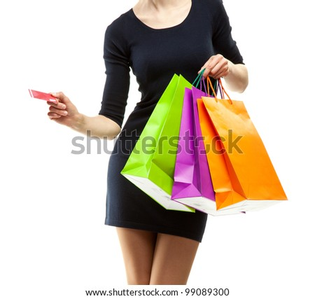 Young woman doing shopping; woman showing paper bags and credit card isolated on white