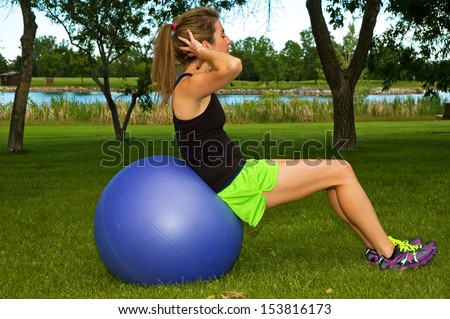 Young woman doing sit ups in a park, on a blue exercise ball.