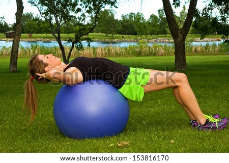 Young woman doing sit ups in a park on an exercise ball. - stock photo
