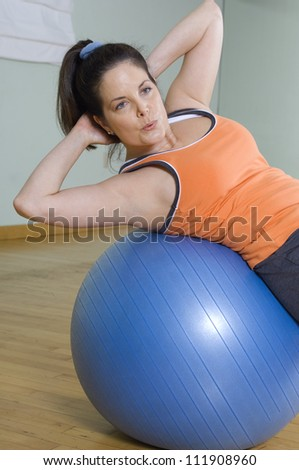 Young woman doing sit-ups on a pilates ball - stock photo