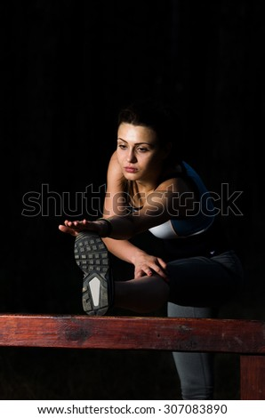 Young woman doing some stretching exercises after running in the forest, soft focus, shallow DOF, low light, some visible noise - stock photo