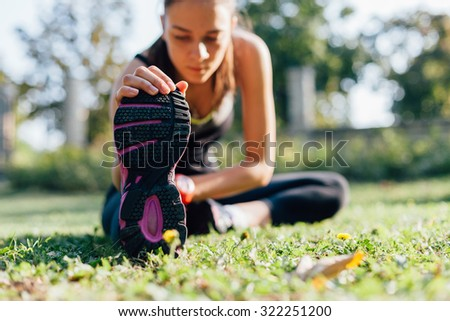 Young woman doing some warm-up exercises before running. - stock photo