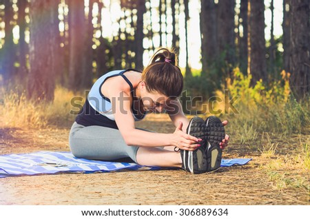 Young woman doing some warm-up exercises before running in the forest.. - stock photo