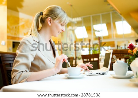 Young woman doing something in laptop. She's sitting in restaurant.