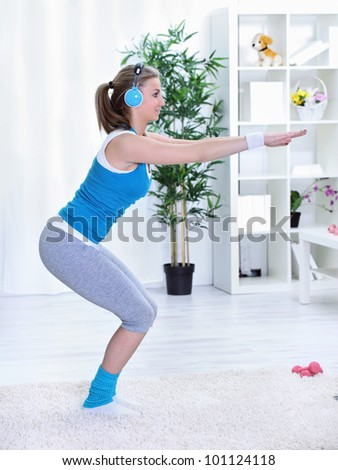 Young woman doing squatting at home