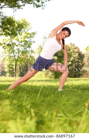 Young woman doing stretching exercise on green grass - stock photo