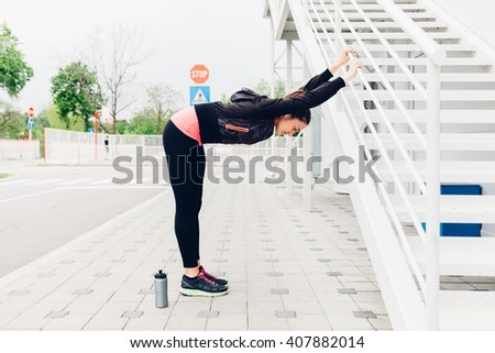 Young woman doing stretching exercises after running in the city - stock photo