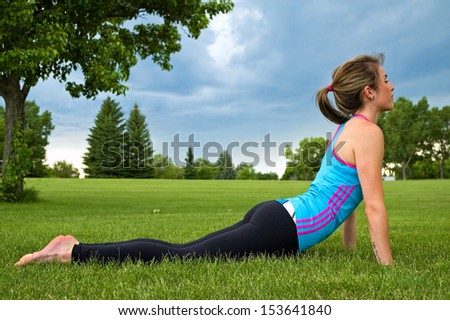 Young woman doing the Cobra Stretch/exercise in a park. - stock photo