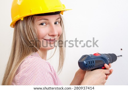 Young woman doing the DIY work and wearing protective helmet - stock photo