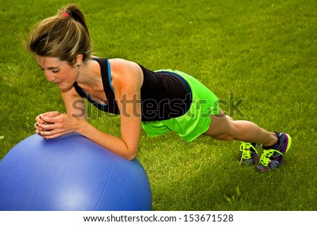Young woman doing the plank with an exercise ball. - stock photo