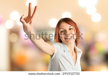 Young woman doing victory gesture on unfocused background - stock photo