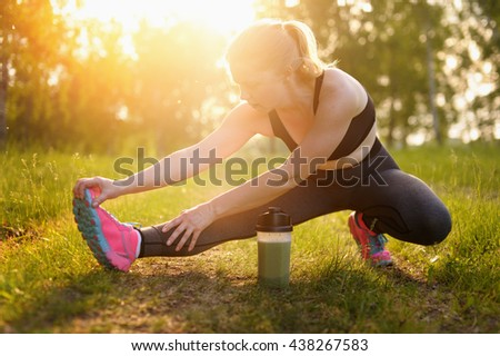 Young woman doing workout on the road at sunset. 