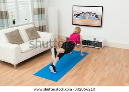 Young Woman Doing Workout While Watching Television In House