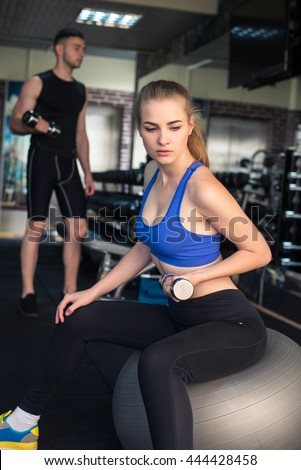 Young woman doing workout with weights on fitness ball in gym