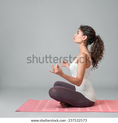 Young woman doing yoga and meditating in lotus position