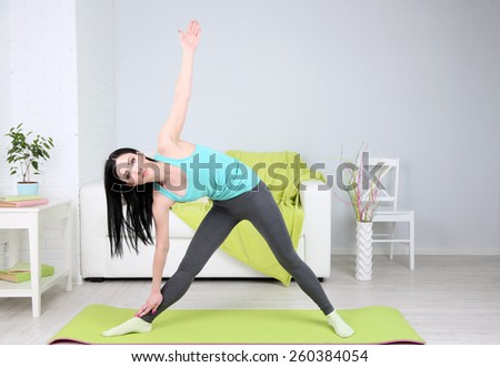 Young woman doing yoga at home - stock photo