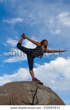 Young woman doing yoga atop a mountain
