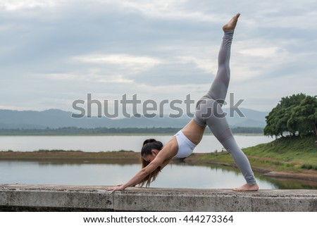Young woman doing yoga exercise in beautiful mountain and lake background