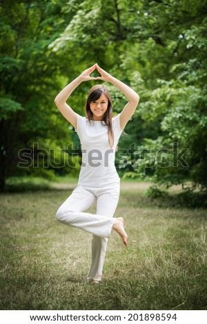 Young woman doing yoga exercise in green park - stock photo